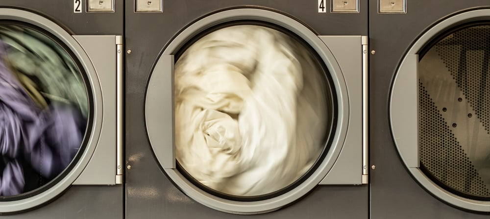 Laundry spinning  in 3 machines alongside each other