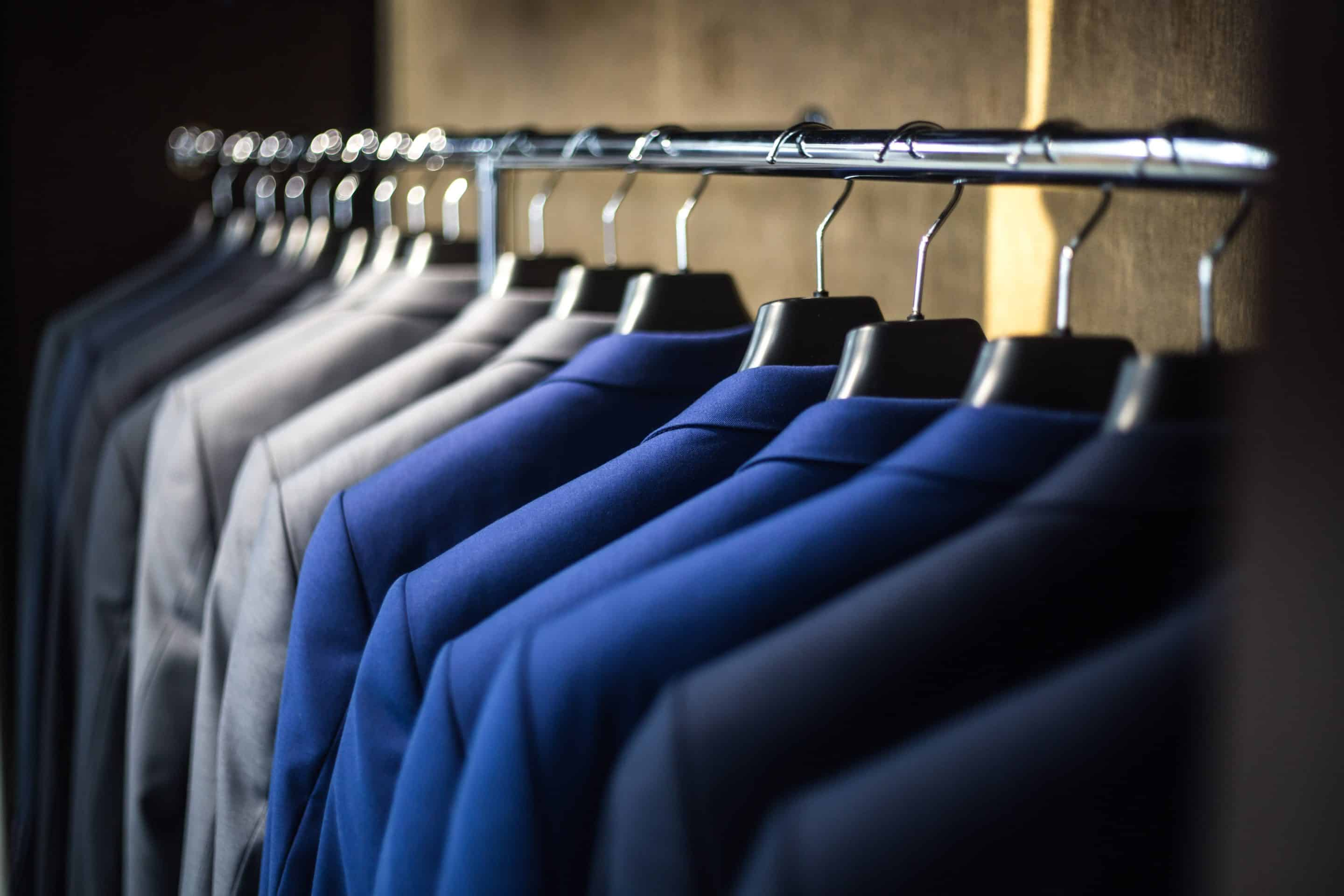 A row of grey and blue shirts hanging